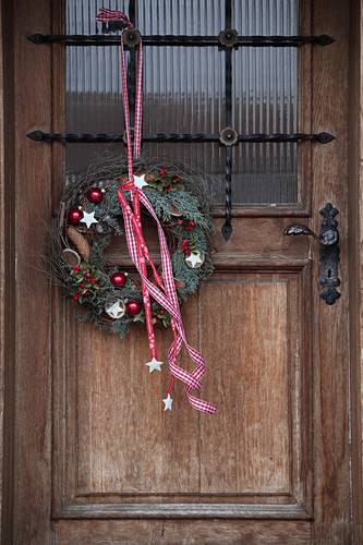 Christmas wreath with red and white ribbon on front door