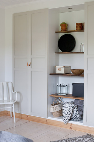 Fitted cupboards with shelving in niche and grey panelled doors