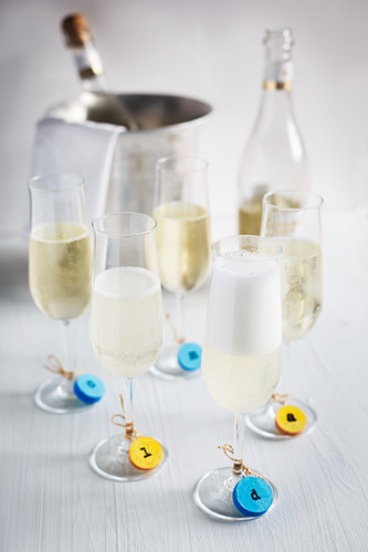 Colourful tags made from corks on glasses of sparkling wine