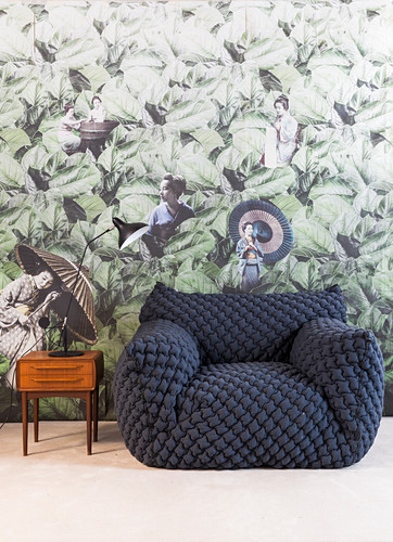 Quilted designer armchair and small retro table against wallpaper with Oriental design
