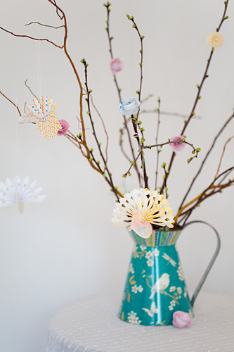Origami birds made from painted paper hung from twigs