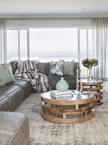 Two round coffee tables made of wood, glass and metal in front of leather sofa
