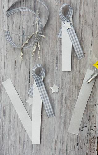 Weihnachtliche Namensschildchen aus Papierstreifen und kariertem Band basteln