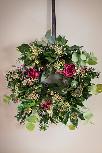 Handmade Christmas wreath with roses on wall