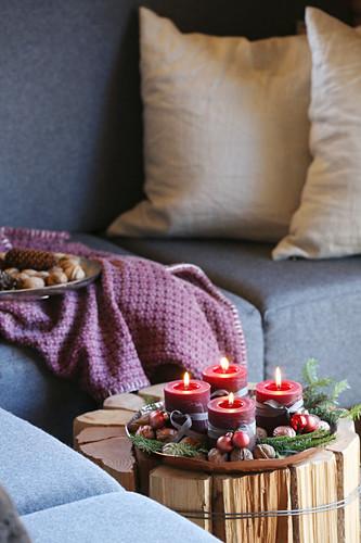 DIY-Beistelltisch aus Holzscheiten, darauf Schale mit Adventskerzen