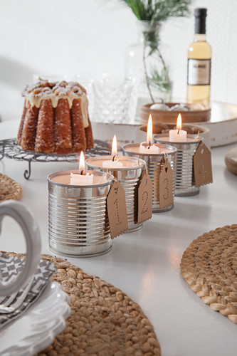 Alternative Advent arrangement of candles in four tin cans in front of Advocaat cake