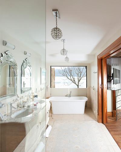 Badezimmer mit Doppelwaschtisch, frei stehender Badewanne und Schiebetür zu Schlafzimmer