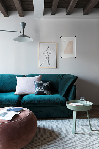 Pouffe and round tray table in front of teal sofa