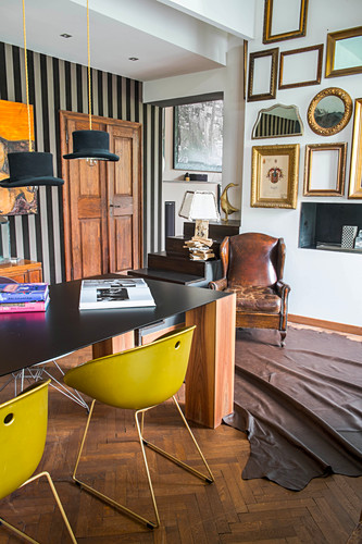 Yellow shell chairs around table with black top and solid wooden legs next to various picture frames on wall