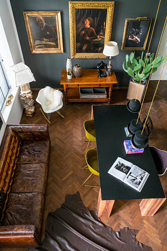 View down onto table, shell chairs, vintage leather couch and gilt-framed pictures
