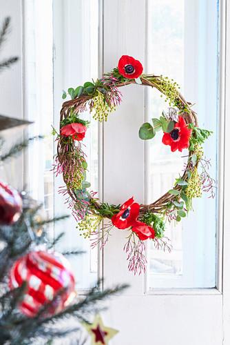 Weihnachtlicher Türkranz mit roten Anemonenblüten