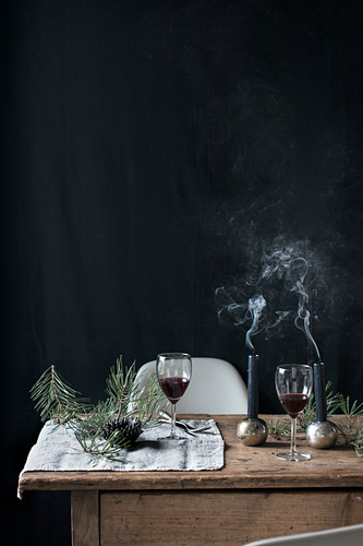 Two glasses of red wine and Christmas decorations on wooden table