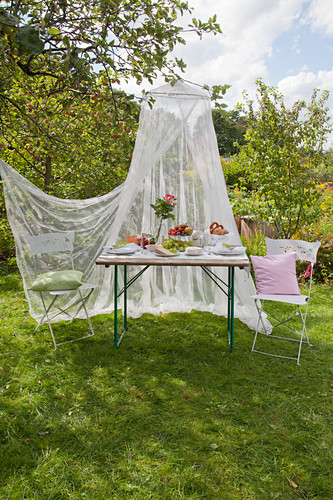 Set garden table and two chairs under mosquito net in garden