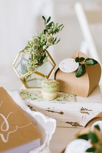Blume in geometrischer Vase, Geschenkkarton und Macarons