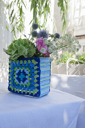 Flowers in vase with crocheted blue-and-green cover