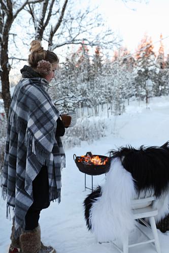 Frau neben Stuhl mit Fell und Feuerschale im Schnee