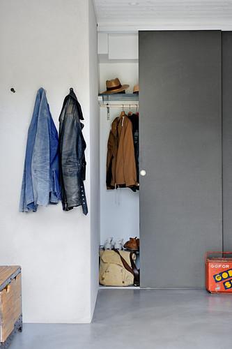 Garderobe hinter grauen Schiebetüren und Wandhaken an weißer Wand