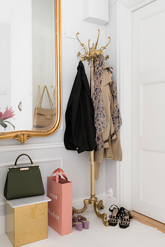 Brass coat stand and gilt-framed mirror in white hallway