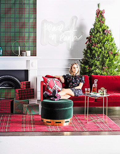 Blonde Frau auf rotem Sofa sitzend vor Weihnachtsbaum, vor Kamin Weihnachtsgeschenke