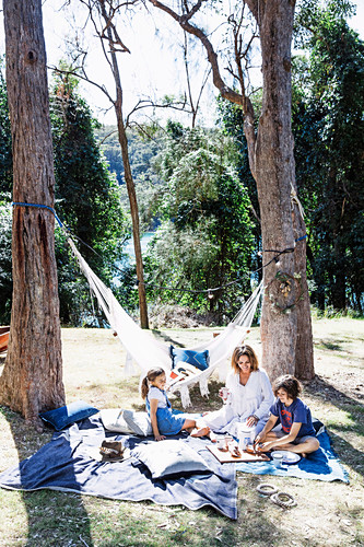 Family picnicking under tall trees in the garden