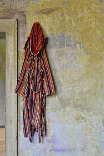 Striped dressing gown hung on vintage-style wall