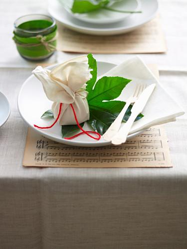 Tischgedeck mit Feigenblatt und Päckchen auf Notenblatt