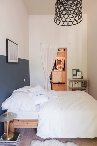 Double bed in narrow bedroom with dressing room in background