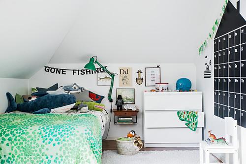 Wandkalender in Hausform im Kinderzimmer mit grüner Deko
