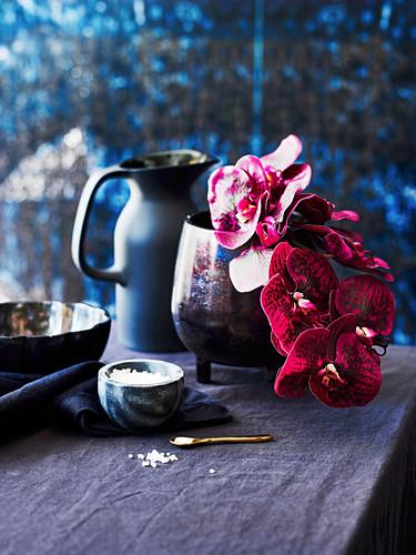 Orchideen in Keramikvase mit Salzschälchen auf grauer Leinentischdecke