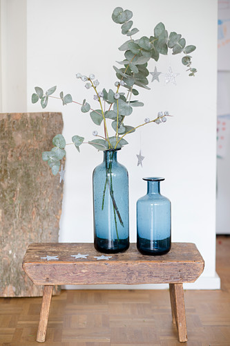 Two blue vases and eucalyptus branches on stool