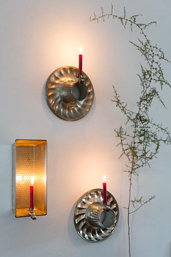 Wandleuchter aus alten Backformen und Kerzen an Kerzenklammern