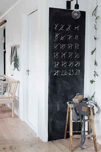 Adventskalender mit Zahlen zum Durchstreichen auf einer Tafel