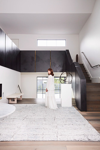 Elegant, minimalist hall with stairs, woman in white dress