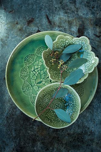 Eucalyptus sprig lying across green ceramic dishes