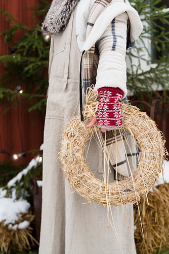 Woman dressed for winter holding straw wreath