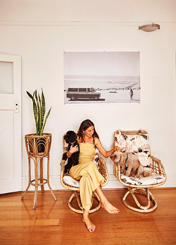 Young woman with two dogs next to houseplant