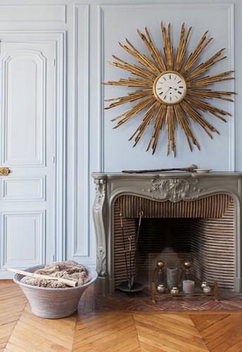 Golden sunburst mirror on wall above antique open fireplace