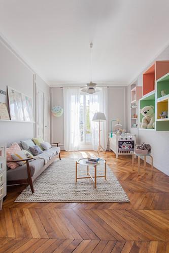 Nursery in pastel shades in period apartment with herringbone parquet floor
