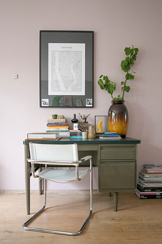 Schwingstuhl und alter Schreibtisch vor rosafarbener Wand