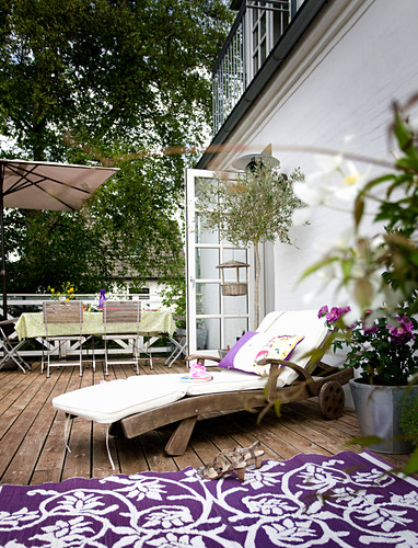 Wooden lounger with cushions and purple and white rug on terrace