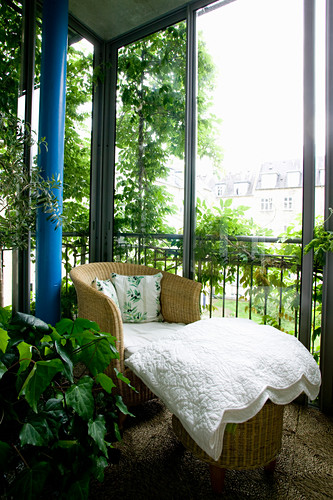 Cushions on wicker armchair on balcony with sliding glass element