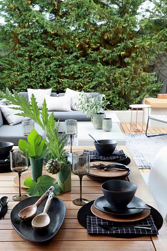 Table set with black crockery on terrace