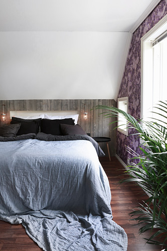 Bedroom with wood-panelled knee wall below sloping ceiling