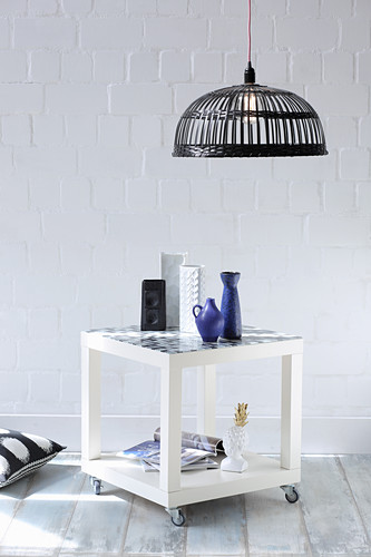 Side table with shelf on castors in front of white wall