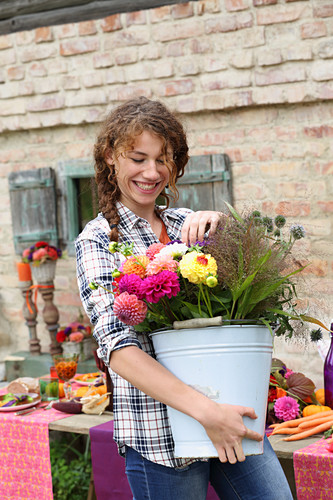 Smiling woman carrying a bucket of brightly coloured autumn flowers