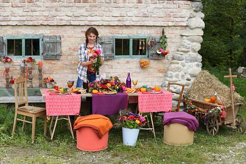 Junge Frau am bunt gedeckten Tisch fürs Erntedankfest