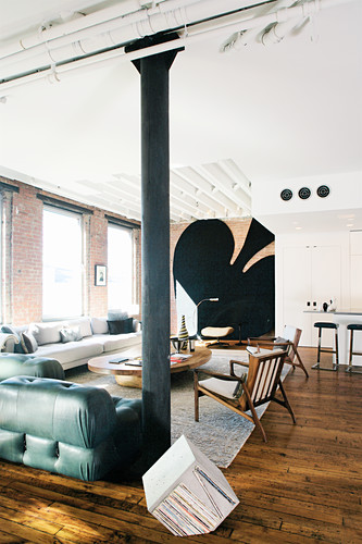 Masculine living area in loft apartment with huge spades symbol in background