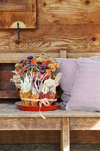 Autumnal bouquet of chrysanthemums and asters in ring of multicoloured corncobs