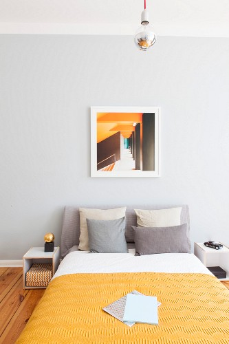 Bed against pale grey wall in bedroom in shades of yellow and grey