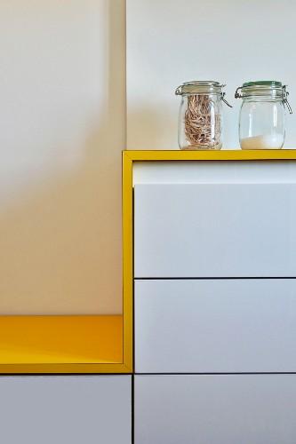 weiße Küchenzeile mit gelber Abstellfläche, übergehend in Sitzbankfläche